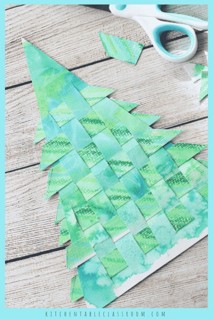 Best Christmas Paper Crafts featured by top Seattle lifestyle blogger, Marcie in Mommyland: Use old recycled artwork to create this woven paper Christmas tree craft. A great introduction to weaving as well as a Christmas craft that you'll keep!