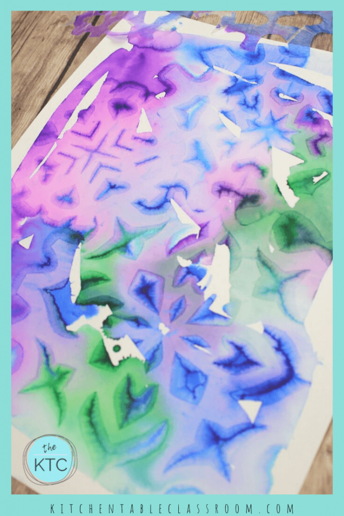 Use cut paper snowflakes to leave detailed impressions in your wet on wet watercolor painting with this easy snowflake painting. #snowflakeart #papersnowflake