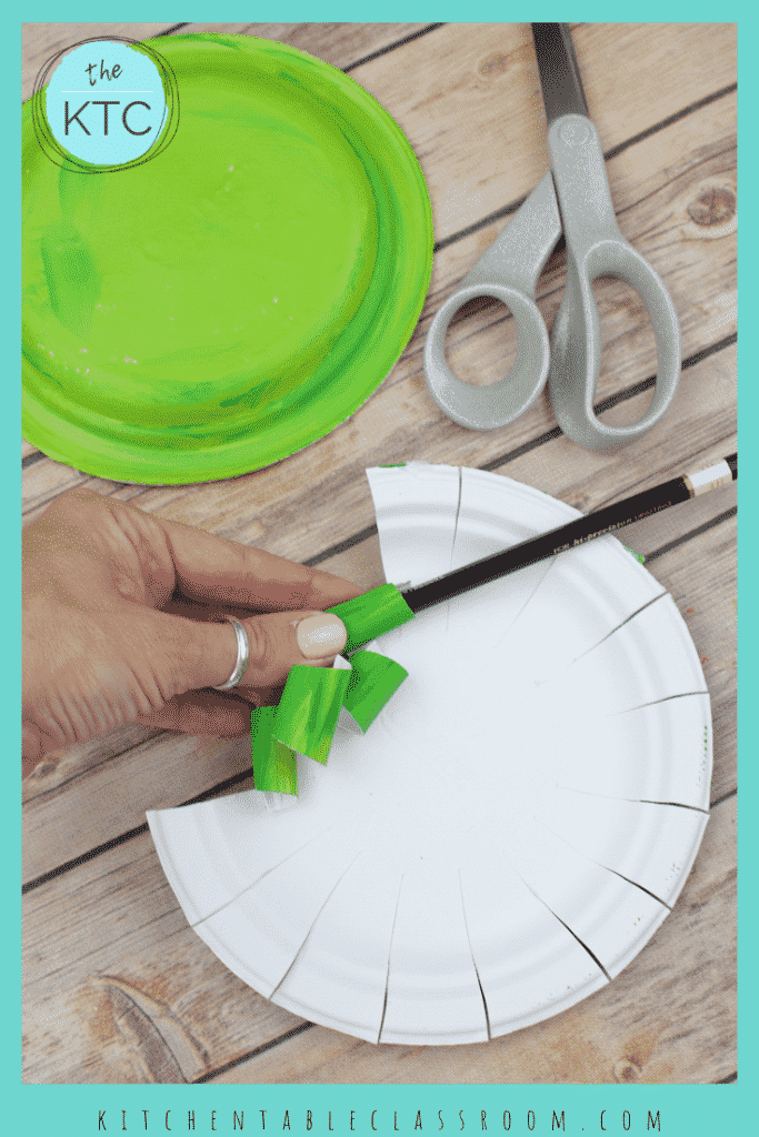 Turn a simple paper plate intro this sweet wreath Christmas ornament. Add a saying inside each paper plate wreath & it becomes a keepsake! #paperplatecraft