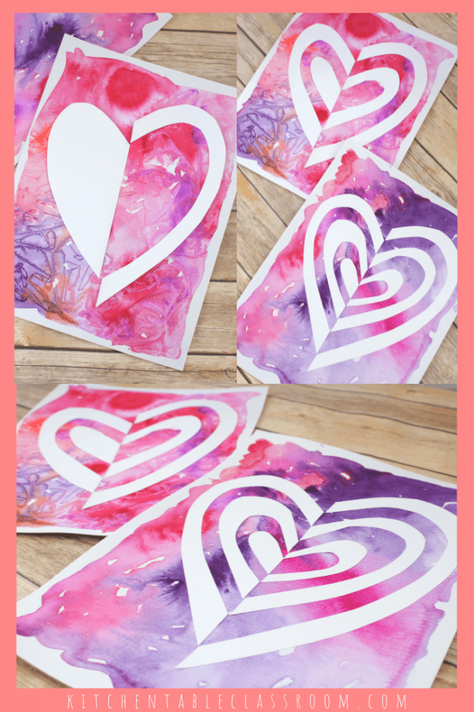 Notan cut paper heart art with pink watercolor background