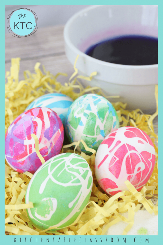 bold colored Easter eggs decorated with rubber cement in a bed of yellow Easter grass