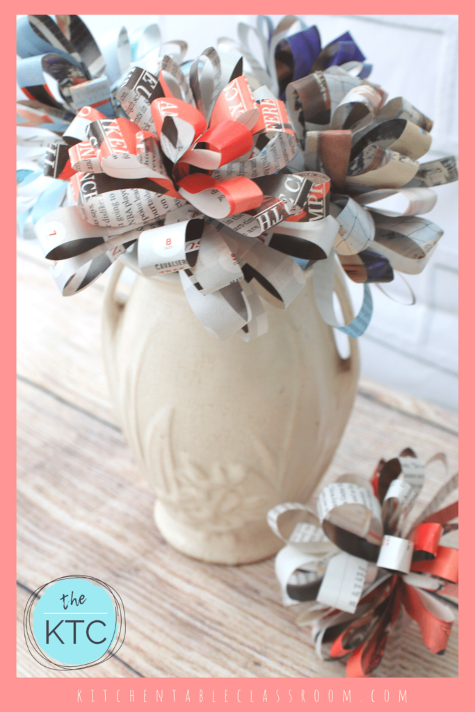 White vase filled with paper flowers made from up-cycled magazine pages