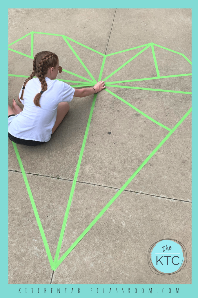 painters tape outlines large heart sidewalk mural to be painted with sidewalk chalk paint
