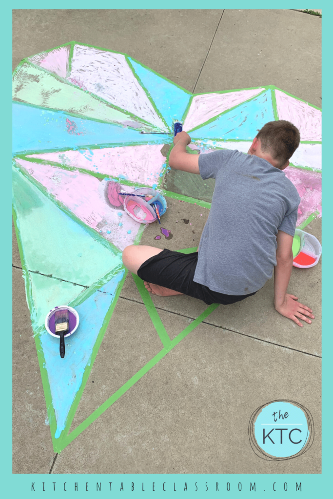 child painting a large heart sidewalk mural