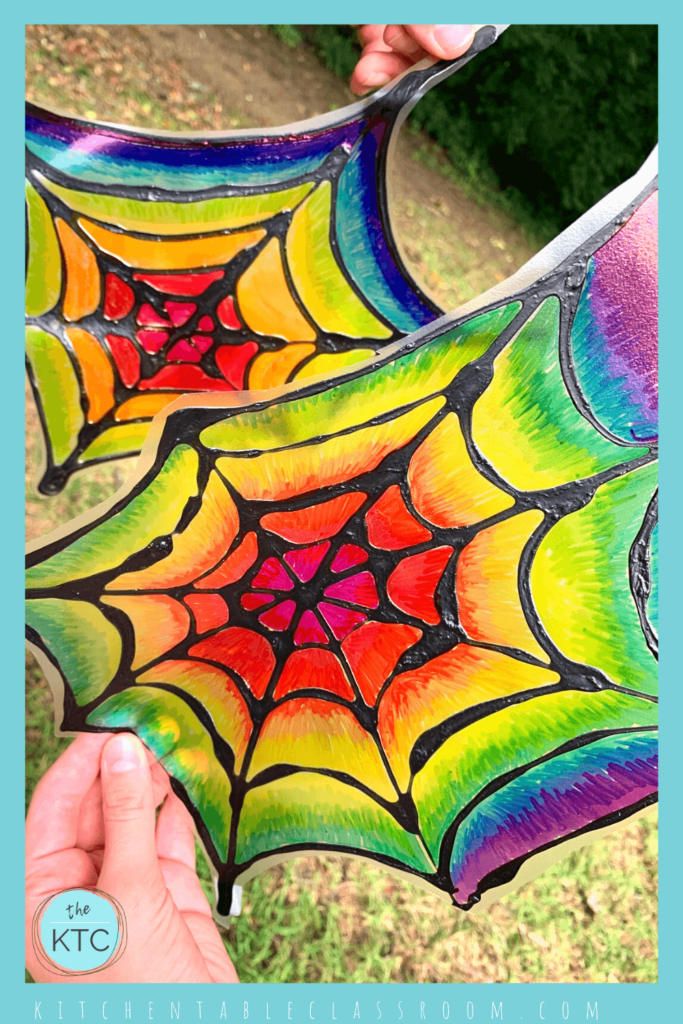 Create rainbow stained glass spiderwebs using permanent markers on poly page protectors.