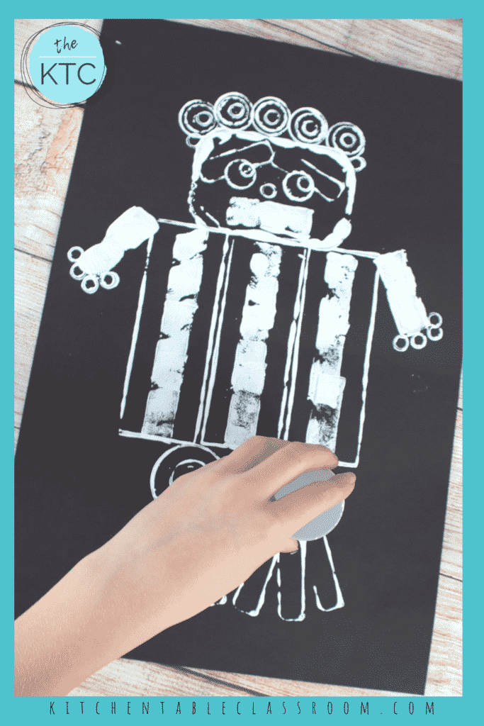 White paint on black paper creates robot prints that are require a super easy set up