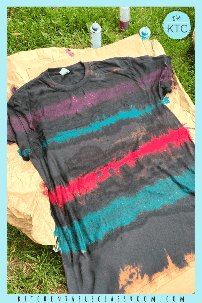 Reverse tie dying soaks previously bleached areas of a dark fabric with colored dye resulting in a bright color tie dye design on a black background.